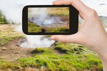 tourist photographs geyser in Haukadalur