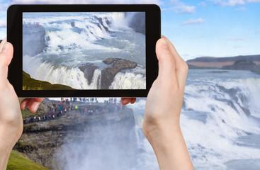 tourist photographs Gullfoss waterfall in autumn