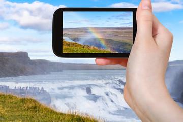 tourist photographs rainbow at Gullfoss waterfall