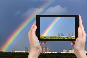 tourist photographs rainbow in dark blue sky