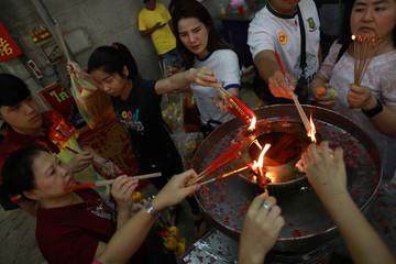 People burn incense sticks during the Lunar New Year celebrations at Wat Mangkon Kamalawat in Chinatown, Ba