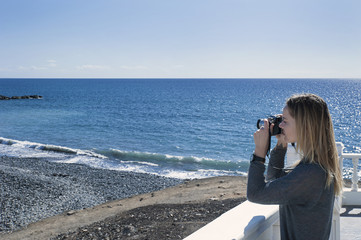 Young millennial female of Caucasian ethnicity holding a camera and taking a photograph facing towards the ocean, the pebble beach and coast in a sunny morning in Tenerife, Canary Islands, Spain
