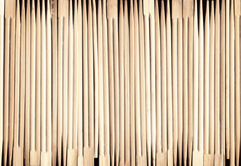 Many Asian wooden chopsticks arranged in a row background. A lot of Chinese traditional eating utensils. Geometrical striped wood pattern