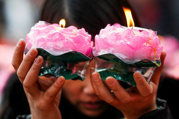 A woman holds candles as she prays at a Buddhist temple in Badachu park during Spring Festival celebrations marking Chinese New Year in Beijing