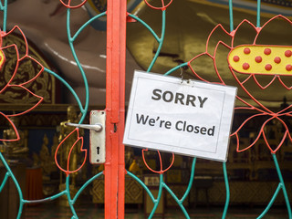 """Door lock with sign board """"sorry we're closed, at the temple"""