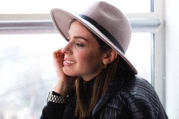 Beautiful boho woman in wool hat sitting by the window