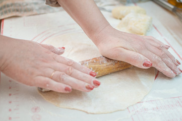 Close-up view of the hands with rolling pin rolling out dough for homemade pizza.