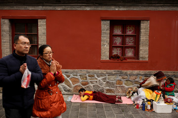 Chinese people make a gesture of prayer as they walk past a Tibetan family at a Buddhist temple in Badachu park during Spring Festival celebrations marking Chinese New Year in Beijing