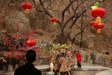 A man watches a boy playing in Badachu park during Spring Festival celebrations marking Chinese New Year in Beijing