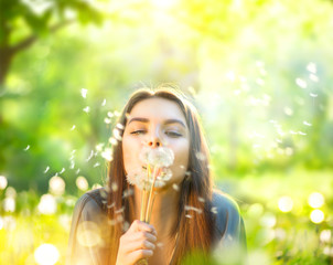 Beautiful young woman lying on green grass and blowing dandelions. Allergy free concept