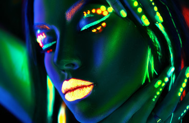 Wall Mural - Fashion model woman in neon light. Portrait of beautiful model girl with colorful fluorescent makeup