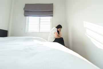 Woman have a headache and feeling serious while sitting on bed after wake up in the morning