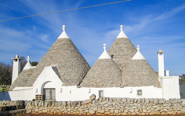 Group of Trulli with symbols, traditional old houses and old stone wall in Puglia, Italy