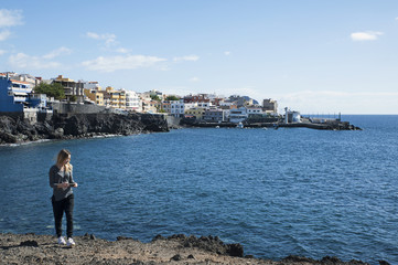 Young millennial female of Caucasian ethnicity holding a phone in the hand and walking away from the coast of Los Abrigos village, in Tenerife, Canary Islands, Spain