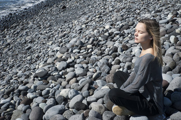 Young blonde Caucasian female sitting in a relaxing, meditating position with eyes closed, wearing a neutral outfit on the beach, in harmony with the surroundings, under the bright morning sunlight