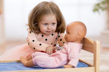 Child toddler in kindergarten. Kid in nursery school. Little girl preschooler playing doctor with doll.