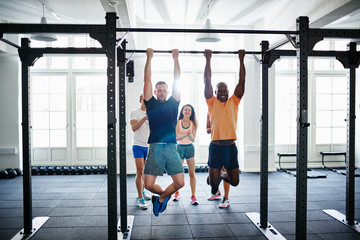 People watching two men doing chin ups in a health club