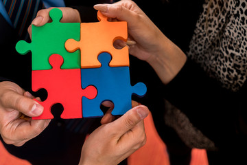 Business people solving jigsaw puzzle. Team holding colorful puzzle pieces in hands