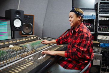 Smiling operator sitting by soundboard in studio, looking at monitor and mixing sounds