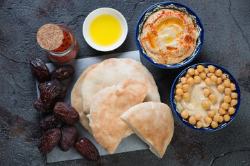 Pita bread, bowls with hummus and dates fruits, view from above, horizontal shot