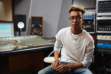 Young African-american deejay in eyeglasses looking at camera while sitting in studio of records