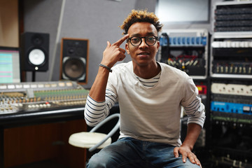 Young record studio staff in jeans, pullover and eyeglasses pointing at his temple and looking at camera