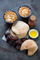 Bowls with creamy hummus, pita bread and dates on a grey weathered asphalt background, selective focus, studio shot
