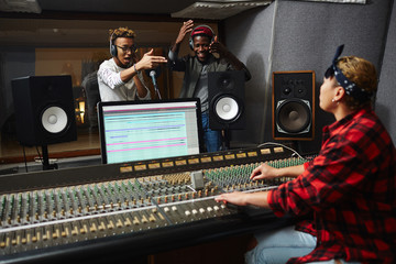 Excited musicians performing their songs in studio in front of operator making records