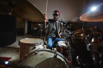 Young drummer and participant of popular band playing drums in studio during repetition