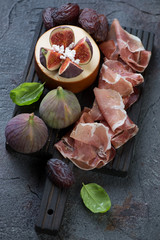 Black wooden chopping board with prosciutto, cheese, fig fruits and dates, vertical shot, selective focus