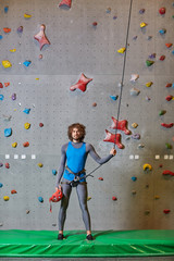 Active guy in blue sportive vest and grey leggins standing on mat and holding by strung climbing rope