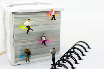 Miniature people: businessman reading newspaper on a big book. Image use for background education or business concept.