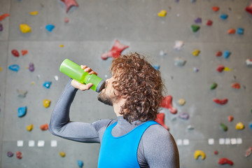 Curly young man drinking water from bottle on background of climbing wall