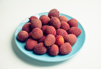 Ripe lychees on the blue plate on white wooden background. Selective focus.