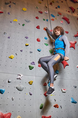 Active guy hanging on strung rope while holding by climbing wall during training
