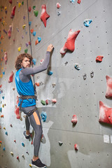 Active sportsman looking at camera while hanging on safety rope by climbing wall during workout