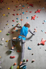 Young sportsman holding by ledges on climb wall while hanging on safety rope and climbing further