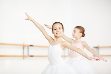 Two little girls outstretching arms while training in ballet class