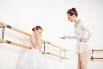 Strict ballet teacher expressing her dissatisfaction while talking to upset little ballerina