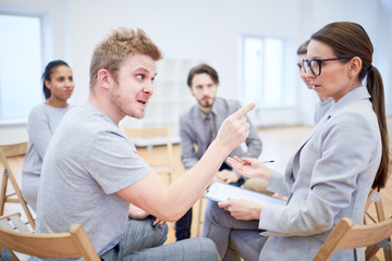 Angry young man pointing at female psychologist during psychological session