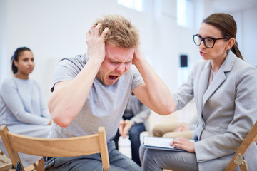 Troubled or stressed young man screaming while psychologist trying to support him during session