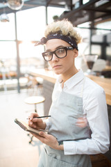 Young waitress in eyeglasses and uniform looking at camera by her workplace