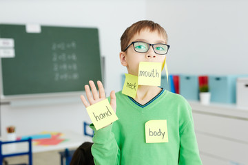 Schoolboy in eyeglasses with body part names written on notepapers stuck on his hand and face