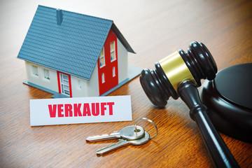 Haus mit einem Auktionshammer. Zwangsversteigerung, Versteigerung, Immobilie, Verkauf, Geschäft, Gerichtsbeschluss