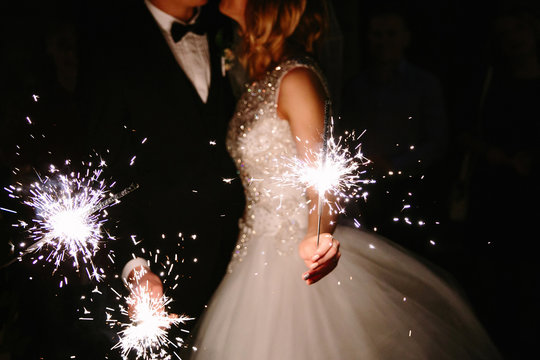 Young happy lyudis sparklers in his hands during the celebration. The bride and groom holding lights in his hands. Glittering lights of the sparklers.