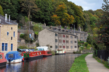 the canal and marina in hebden bridge with boats on the water, towpath and surrounding hillside trees