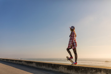 Cute girl with skateboard near the beach at sunset