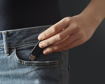Young woman pushing usb flash drive into a pocket