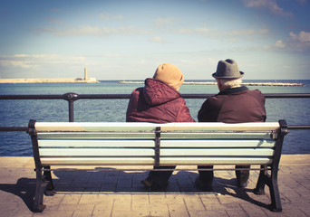 Elderly lovely couple on a bench by the sea