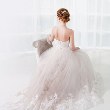 Back view of amazing young bride. Red head woman seat on the chair. Elegant hairstyle.